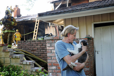 The owner of a cat rescued from a burning house hugs his feline after firefighters gave the cat oxygen in the 21900 block of Woodland Crest Dr. in Woodland Hills, CA.  Tuesday, April 12, 2011. (Hans Gutknecht/Staff Photographer)