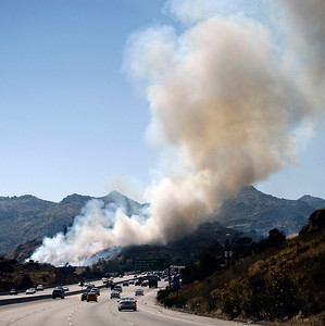 Firefighters from LA City, LA County and Ventura County battle a brush fire along the west bound 118 freeway west of Topanga Cyn Rd. The fire burn up to 10 acres and closed two lanes of the west bound 118 freeway backing up traffic for miles. The caused is under investigation in Chatsworth CA  July 8,2010. Photo by Gene Blevins/LA Daily  News