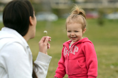 Chloe Caplon 2-year-old, and nanny Sunny Morales play with dandelions at Holleigh Bernson Memorial Park in Porter Ranch Tuesday, March 1, 2011. (Hans Gutknecht/Staff Photographer)