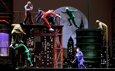 """Cops and Robbers play out a scene flying through the skyline from one hidden trampoline to another. Cirque du Soleil will present IRIS, a new major, resident production created exclusively for the Kodak Theatre at the Hollywood & Highland Center, home of the Academy Awards® with preview performances starting July 21, 2011. According to Cirque, IRIS is, """"A poetic phantasmagoria inspired by the world of cinema, IRIS presents an imaginary journey through the evolution of cinema – from the foundations of the art form to the bustle of the soundstage – through optical effects and film genres."""" Hollywood, CA 6-16-2011. (John McCoy/Staff Photographer)"""