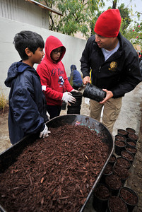 (l-r) Hector Miranda,11, and Justin Mazariego,11, work with State Assemblymember Felipe Fuentes as they fill pots with mulch. Students, elected officials, and community members worked together to improve a blighted pedestrian bridge. The Haddon Avenue pedestrian bridge spans the Pacoima Wash and links San Fernando High School to the rest of Pacoima. This bridge is used by over 200 students and community residents every day. The bridge currently suffers from sever blight and neglect with graffiti, peeling paint covering its surfaces and trash littering the surrounding area. Pacoima, CA.11-20-2010. (John McCoy/staff photographer)