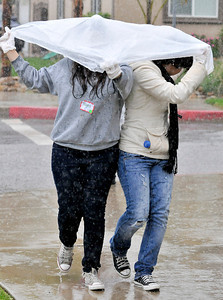(l-r) Mayra Romero,17, and Jocelyne Gonzalez,17, try to keep dry under a plastic trash bag.  Students, elected officials, and community members worked together to improve a blighted pedestrian bridge. The Haddon Avenue pedestrian bridge spans the Pacoima Wash and links San Fernando High School to the rest of Pacoima. Over 200 students and community residents use this bridge every day. The bridge currently suffers from sever blight and neglect with graffiti, peeling paint covering its surfaces and trash littering the surrounding area. Pacoima, CA.11-20-2010. (John McCoy/staff photographer)