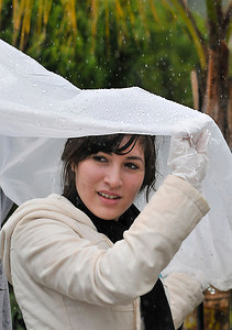 Jocelyne Gonzalez,17, tries to keep dry under a plastic trash bag.  Students, elected officials, and community members worked together to improve a blighted pedestrian bridge. The Haddon Avenue pedestrian bridge spans the Pacoima Wash and links San Fernando High School to the rest of Pacoima. Over 200 students and community residents use this bridge every day. The bridge currently suffers from sever blight and neglect with graffiti, peeling paint covering its surfaces and trash littering the surrounding area. Pacoima, CA.11-20-2010. (John McCoy/staff photographer)