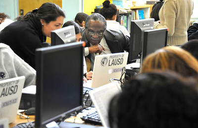 (C) William Mulholland Middle School principle John White works with kids during the Computers for Youth Los Angeles Launch Family Learning Workshop as parents and children work together and then take their home learning center with them at the end of the day at William Mulholland Middle School in Van Nuys. Dec 4 ,2010. Photo by Gene Blevins/LA Daily News