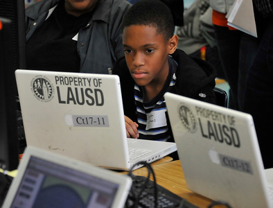 Dameon Williams works and learns on a laptop during the Computers for Youth Los Angeles Launch Family Learning Workshop as parents and children work together and then take their home learning center with them at the end of the day at William Mulholland Middle School in Van Nuys. Dec 4 ,2010. Photo by Gene Blevins/LA Daily News