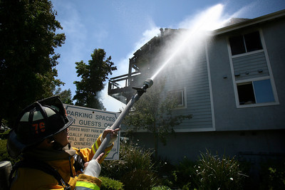 CONDO FIRE--Firefighters work to put out a large fire in a condominium at 26853 Claudette in Canyon Country, CA.  The fire began after an explosion was heard in one of the units shortly after noon Wednesday. David Crane/Staff Photographer