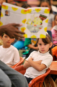 "Perla Garcia,5, in the first grade, listens to Fowler read his book. Seth Fowler is a Woodland Hills resident who is enrolled at Morehouse College. When he was 9-years old, he wrote an illustrated a book ""Cory the Popcorn's Big Adventure,"" that has since been published. He was invited to read an excerpt from his book at 75th Street Elementary School. Los Angeles, CA 08/04/2010 (John McCoy/Staff Photographer)"
