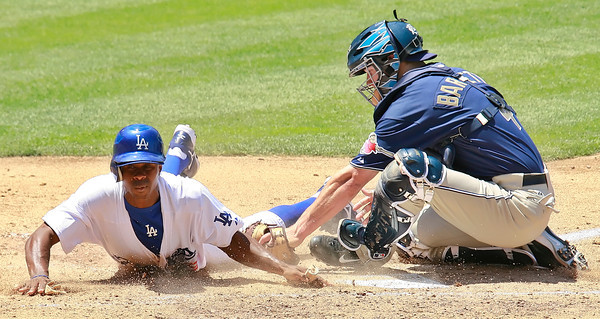 Los Angeles Dodgers' Juan Pierre slides across home plate avoiding a tag by San Diego Padres' Michael Barrett to bring in the third run in the third inning of the game played at Dodgers Stadium in Los Angeles, CA, on Sunday, July 1, 2007 where the Dodgers won with the final score of 5-0.   (John Lazar/L.A. Daily News Staff Photographer)