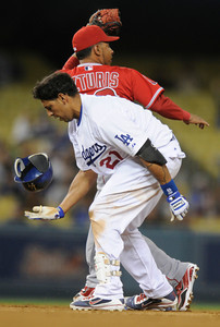 Juan Rivera makes has his hat in hand after stealing 2nd base against Maicer Izturis in the 2nd inning. Dodgers played host to the Angels in a pre-season game that is known as the Freeway Series. Los Angeles, CA 4/3/2012(John McCoy/Staff Photographer)