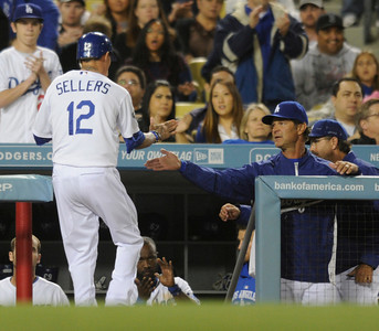 Justin Sellers (12)  is congratulated by Dodger Manager Don Mattingly  after being driven in by a sacrifice fly off the bat of Matt Kemp in the 5h inning. Dodgers played host to the Angels in a pre-season game that is known as the Freeway Series. Los Angeles, CA 4/3/2012(John McCoy/Staff Photographer)