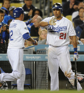 Justin Sellers (12)  is congratulated by Juan Rivera (21) after being driven in by a sacrifice fly off the bat of Matt Kemp in the 5h inning. Dodgers played host to the Angels in a pre-season game that is known as the Freeway Series. Los Angeles, CA 4/3/2012(John McCoy/Staff Photographer)