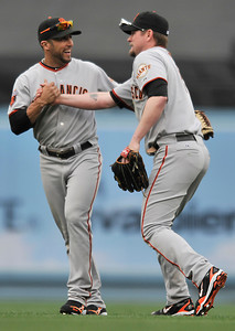 Giants CF Aaron Rowand congratulates Aubrey Huff on a diving catch on a ball hit by Tony Gwynn Jr. to end the 8th inning. The Los Angeles Dodgers hosted the San Francisco Giants in a game at Dodger Stadium in Los Angeles, CA 4-1-2011. (John McCoy/staff photographer)