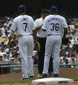 Dodgers trainer came out to check out Roberto Hernandez's hands after getting injured throwing the ball to first baseman James Loney to tag New York Mets' Lastings Miledge out at first base. (Edna T. Simpson)