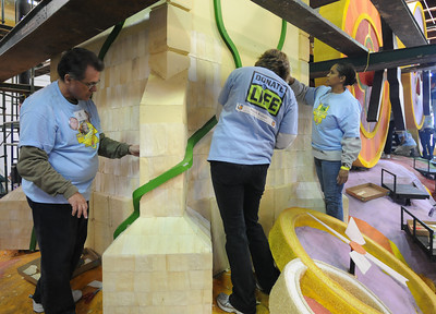 """Hundreds of volunteers gathered at the Rose Bowl Float Pavilion to decorate the Donate Life Rose Parade Float. The float honors organ donors and recipients, and will feature 28 riders who have all given or received organ transplants. The float features six enormous floral timepieces that will be adorned with 72 memorial """"floragraphs'"""" depicting deceased donors whose gifts game life and time to so many. The float features a 33-foot clock tower that has hands that turn backwards to remind us to make each passing day count. Pasadena, CA 12/27/2011(John McCoy/Staff Photographer)"""