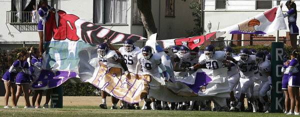Bell Football players break through the paper sign as  cheerleaders and fans cheer them on at the begining of second half of the game against Eagle Rock on Friday, September 21, 2007 . (Edna T. Simpson)