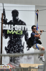 Matthew Serrano,19 of Van Nuys, uses his video camera to shoot action on the zip line. Thousands of fans of the video game Call of Duty descended on the Stags at Playa Vista to experience the release of a new version of the game. Hundreds of monitors where available for people to try out the new game. In addition, attendees could also experience real-life Call of Duty thrills, including paintballing in a recreated, life-size Call of Duty map, Sumo wrestle or go for a ride on a zip line. Playa Vista, CA. 9-3-2011. (John McCoy/Staff Photographer)