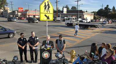 LAPD officers, Councilmember Paul Krekorian and Gabriel Avila, uncle and godfather of the victim talk to the media and area residents about the fatal accident.  At the same time, a pedestrian is crossing the street as a tow truck illegally passes thru the crosswalk.   Officials and North Hollywood residents demand the installation of a traffic signal at a busy intersection where a 12-year-old girl was hit by an SUV and later died.  Emely Aleman, 12, was taken off life support Thursday and Angela Rodriguez, 10, who was also struck in the Tuesday incident, remained hospitalized with critical injuries as a result of their being hit by a Jeep Wrangler while they were in a crosswalk at Laurel Canyon Boulevard and Archwood Street.  (Dean Musgrove/Staff Photographer)