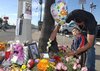 Hector Barut and his 17 month-old son Jeffrey, visit the curbside memorial.  Officials and North Hollywood residents demand the installation of a traffic signal at a busy intersection where a 12-year-old girl was hit by an SUV and later died.  Emely Aleman, 12, was taken off life support Thursday and Angela Rodriguez, 10, who was also struck in the Tuesday incident, remained hospitalized with critical injuries as a result of their being hit by a Jeep Wrangler while they were in a crosswalk at Laurel Canyon Boulevard and Archwood Street.  (Dean Musgrove/Staff Photographer)