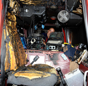 LA county firefighter Chuck Lopez looks at the damage to their fire engine after one of the few explosions sent flying chunks of titanium metal into rig that set the inside on fire.  M  Los Angeles CA. July 14,2010.  Photo by Gene Blevins/LA Daily News