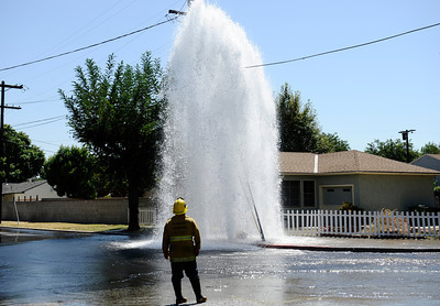 LA city firefighters and DWP look to turnoff the water shooing into the air from a fire hydrant that was knock off by a semi truck trying to turn in the narrow streets at intersection of  Saticoy and Balboa. DWP was able to shut off the water in 45 minutes and no homes were damage in Van Nuys, CA.   Aug 29,2011 photo by Gene Blevins/LA DailyNews