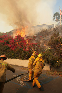 MALIBU FIRE--A firefighter puts water on a flare up along Pacific Coast Highway.   Photo by David Crane/Staff Photographer.