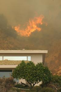 MALIBU FIRE--Flames erupt above a home along Pacific Coast Highway sunday.  Photo by David Crane/Staff Photographer.