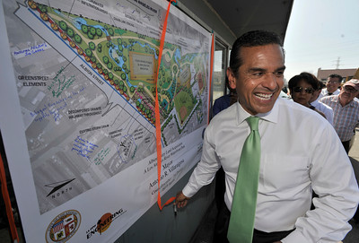 Mayor Antonio Villaraigosa turns with a smile after autographing a poster showing what the new park will look like. Villaraigosa and First District Councilman Ed Reyes kicked off the demolition of the old Albion Dairy site to make way for a future Los Angeles River park. The pair climbed into matching 330-Caterpillars and pushed over one of the last remaining walls of the old dairy building. Lincoln Heights, CA 9/29/2011(John McCoy/Staff Photographer)