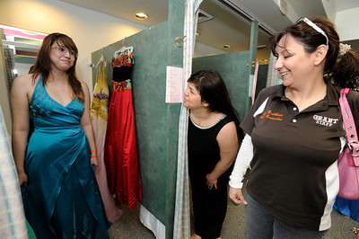 """(l-r) Iris Corona gets approval from her friend Wendy Arredondo and Grant High School councilor Amy Bazikian. For the fourth consecutive year, the Los Angeles Unified School District (LAUSD) Homeless Education Branch will partnered with Operation School Bell to fulfill 38 teenage girls' dream of wearing the perfect dress on prom night. The lucky girls, identified as either homeless or from low-income families, have been chosen from throughout the District to select """"the"""" dress from a closet filled with formals, after-five, evening attire and party dresses ranging in sizes from 0 to 16. The fantasy closet features dresses designed in an array of colors and styles, including full-length, mini, satin, lace and strapless creations. Shoes and accessories will also be provided to complete their ensemble and prom dream. Hollywood, CA 5-6-2011. (John McCoy/staff photographer)"""