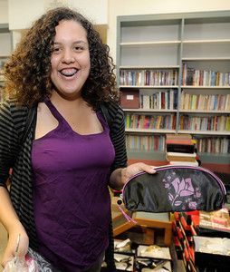 """Maria Salazar found just the right hand-bag for her dress. For the fourth consecutive year, the Los Angeles Unified School District (LAUSD) Homeless Education Branch will partnered with Operation School Bell to fulfill 38 teenage girls' dream of wearing the perfect dress on prom night. The lucky girls, identified as either homeless or from low-income families, have been chosen from throughout the District to select """"the"""" dress from a closet filled with formals, after-five, evening attire and party dresses ranging in sizes from 0 to 16. The fantasy closet features dresses designed in an array of colors and styles, including full-length, mini, satin, lace and strapless creations. Shoes and accessories will also be provided to complete their ensemble and prom dream. Hollywood, CA 5-6-2011. (John McCoy/staff photographer)"""