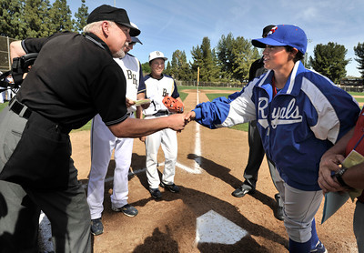 Home plate umpire Larry Crino shakes hands with  San Marcos Pitcher Ghazaleh Sailors as the two teams exchange lineups before the game. Birmingham High Pitcher Marti Sementelli and San Marcos Pitcher Ghazaleh Sailors have the distinct honor of breaking down one of baseballÕs gender barriers, becoming the first females to start against each other in a high school baseball game. Birmingham Sementelli pitched her way to a 6-1 victory. Van Nuys, CA. 3-5-2011. (John McCoy/staff photographer)