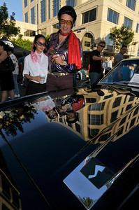 """Yesenia Monterroso,19, and Steve Fowlow,47, are reflected in the hood of a 1963 Studebaker Avante R-2. Brand Blvd south of the Ventura Freeway was closed down for Cruise Night. Hundreds of cars were on display while Beach Boys tribute band """"Surfin' Safari and Chubby Checker entertained the crowd. Later in the evening, Checker tried to break into the record books by getting 5000 people to dance """"The Twist"""". Glendale, CA 07/17/2010 (John McCoy/Staff Photographer)"""