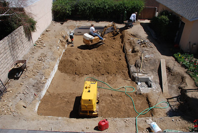 Workers dump dirt into the pool space in Phil and Cil Rivera's Granada Hills backyard.