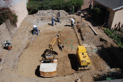 Smoothing out the poured-in dirt in the unused pool in Phil and Cil Rivera's Granada Hills backyard.