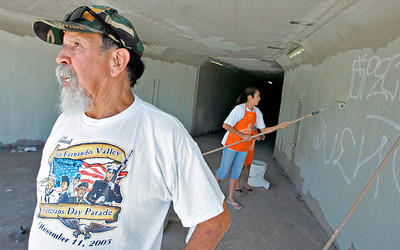 Joe Lazano of Mission Hills, CA, along with his granddaughter Danielle Coronado, 13, and her sister Michelle, 9, (not seen in photo) of Granada Hills who help him paint over some graffiti near San Fernando High School on Wednesday, July 18, 2007. (John Lazar/L.A. Daily News Staff Photographer)