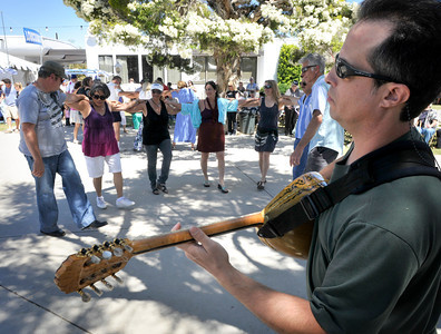 Jim Karidakis plays a Bouzouki while people do a traditional line style Greek dance. The 36th Annual Valley Greek Festival is being held at St. Nicholas Church 9501 Balboa Blvd. in Northridge. Officials at the festival expect an attendance of over 50,000 durning the 3-day event. The admission-free fundraiser is the largest festival of its kind in the area and features Greek live music, dancing, gourmet food, homemade pastries, cooking demonstrations, children's activities, a Greek market, and a variety of shopping boutiques. Northridge, CA 5/29/2010. photo by John McCoy/staff photographer