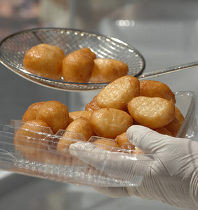 Loucoumathes, or Greek donuts, are put into a container for a customer. The 36th Annual Valley Greek Festival is being held at St. Nicholas Church 9501 Balboa Blvd. in Northridge. Officials at the festival expect an attendance of over 50,000 durning the 3-day event. The admission-free fundraiser is the largest festival of its kind in the area and features Greek live music, dancing, gourmet food, homemade pastries, cooking demonstrations, children's activities, a Greek market, and a variety of shopping boutiques. Northridge, CA 5/29/2010. photo by John McCoy/staff photographer