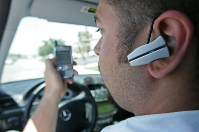 Jack Katchikian, store manager of American Connections Sprint Preferred Partner in Santa Clarita, CA, wears his bluetooth ear piece as he sits behind the wheel of his car and talks on his mobile phone on Thursday, June 28, 2007. (John Lazar/L.A. Daily News Staff Photographer)