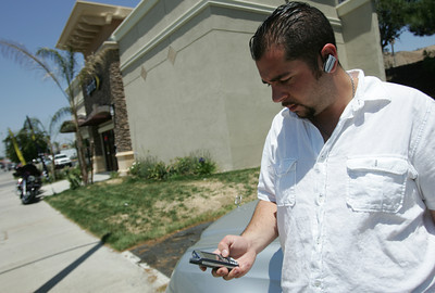 Jack Katchikian, store manager of American Connections Sprint Preferred Partner in Santa Clarita, CA, wears his bluetooth ear piece as he talks on the phone and gets ready to sit behind the wheel of his car on Thursday, June 28, 2007. (John Lazar/L.A. Daily News Staff Photographer)