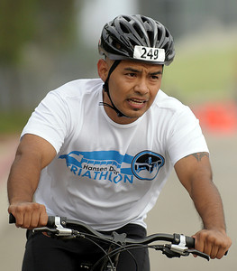 A triathlon participant begins the 11-mile bike ride which loops around the park on Foothill Boulevard, and Wentworth and Osbourne Streets. An estimated 1,000 participants took on the Hansen Dam Triathlon at Hansen Dam Aquatic Center in Lake View Terrace, Calif. on Sunday, Aug. 21, 2011. The course  included a 500-yard open water swim, an 11-mile scenic bike ride through rolling hills, and a 3-mile run through Hansen Dam Regional Park.  (Maya Sugarman/Staff Photographer)