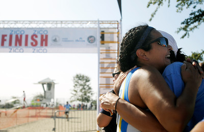 "Alma Zavala of West Hollywood embraces her UCLA Triathlon teammate, Sonia Mason, after finishing her first triathlon ever. Zavala joined UCLA's team only a month ago. ""I know it's me out there,"" said Zavala while crying, ""but without them I wouldn't have made it."" An estimated 1,000 participants took on the Hansen Dam Triathlon at Hansen Dam Aquatic Center in Lake View Terrace, Calif. on Sunday, Aug. 21, 2011. The course  included a 500-yard open water swim, an 11-mile scenic bike ride through rolling hills, and a 3-mile run through Hansen Dam Regional Park.  (Maya Sugarman/Staff Photographer)"