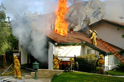 "A house fire broke out at 7345 Alpine Way, Tujunga, CA.  The fire was called into the 911 operator by Paul Phillips, president of the Alpine Village Home Owners Association at 8:14 am today (3/28/12).  The fire was started by a portable electric space heater placed too close to a couch in the garage. Flame caused extensive fire damage to the garage.  The fire traveled into the attic of the house, but before it could ignite the living quarters, firefighters from LAFD 24, 74, 77, and 89 vented the roof and began laying water into the attic and garage areas.  The owner of the house and his two children and three dogs could only sit and watch as smoke streamed out of the residence. The fire was contained in the garage area and parts of the attic.  ""This is what we train for"" stated Fire Station 24 Captain Valdez.   It took 27 firefighters 26 minutes to knockdown the fire.  Photo Credit: David DeMulle'"