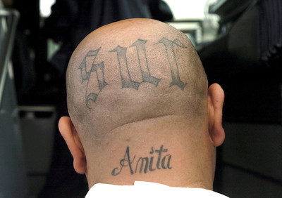 An alleged gang member with a tattoo on his head is arrested by U.S. Immigration and Customs Enforcement agents on Friday morning, Oct.5, 2007, for immigration and criminal violations in the San Fernando Valley.  They were put on a Homeland Security bus and taken to downtown Los Angeles.(Tina Burch/Staff Photographer)