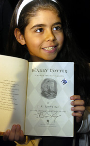 "Estefany Delgadillo, 8, a 4th grader a Huntington Park Elementary School holds her signed ""Harry Potter and the Deathly Hallows"" by author J.K. Rowling at the Kodak Theatre in Hollywood, Ca., on Monday morning, Oct.15, 2007 during the author's open book tour.  (Tina Burch/Staff Photographer)"