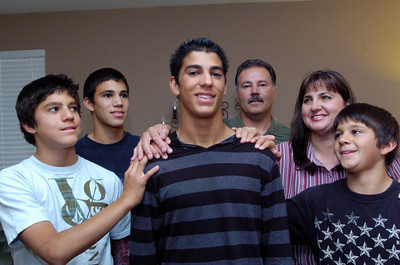 Highland High School cross country runner Jeremy Acosta(center) and his family L to R brothers Paul,11 and Aaron,15,  father Louis, mother Susanlee(cq) and brother Luke,13 at their Palmdale home. (Jeff Goldwater/Special to the Daily News)
