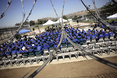 Students get their certificates behind razor wire at the MERIT graduation program at Pitches Honor Ranch thursday.   The 12 week course teaches life skills to inmates serving at the county jail . (David Crane/Staff Photographer)