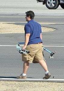 A crew member at Whiteman Airport in Pacoima removes parts left on the tarmac after KCAL/KCBS' Sky9 helicopter made a hard landing Friday, Nov. 12, 2010, at Whiteman Airpark in Pacoima. Engine failure has been cited as the cause. (Gene Blevins/Special to the Daily News)