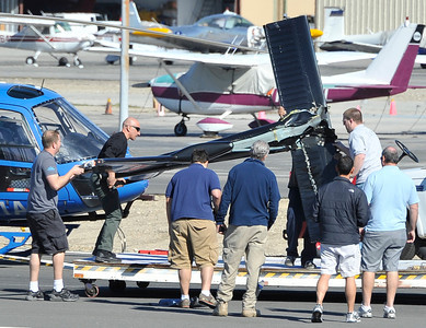 Crew members move the tail rotor of the helicopter KCAL/KCBS pilot Derek Bell was flying after he made a hard landing Friday, Nov. 12, 2010 at Whiteman Airport in Pacoima. Engine failure has been cited as the cause. (Gene Blevins/Special to the Daily News)