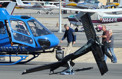 KCAL/KCBS pilot Derek Bell and others look over the helicopter Bell was flying after he made a hard landing Friday, Nov. 12, 2010 at Whiteman Airport in Pacoima. Engine failure has been cited as the cause. (Gene Blevins/Special to the Daily News)