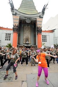"""The Coalition of Kaiser Permanente Unions was in town to hold meetings at the Hollywood Highland and took time out to stage a """"flash mob"""" performance in front of Graumans Chinese Theatre. Hundreds of Kaiser care givers assembled for a 4-minute dance performance staged to promote getting healthy through proper diet and exercise. Representatives from Graumans informed the group that they were trespassing, and ordered them off the property. Hollywood, CA 3/23/2012(John McCoy/Staff Photographer)"""
