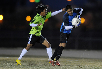 Palmdale#4 Nelson Rivera and Knight#25 Hector Leon mix it up. Knight defeated Palmdale 3-2 in a Golden League boys' soccer match. Palmdale, CA 2/1/2012(John McCoy/Staff Photographer)